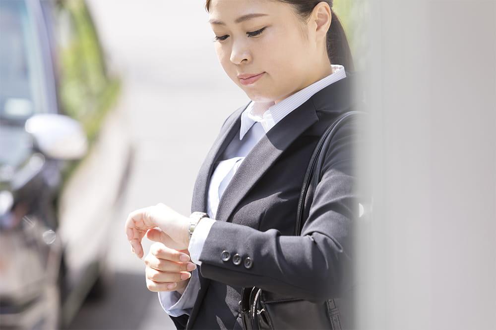時間を気にするスーツを着た日本人女性