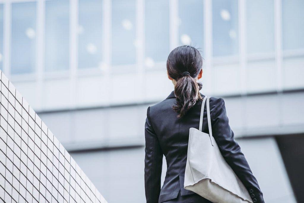 ビルの前に立つリクルートスーツを着た女性