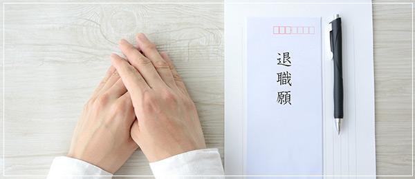 手の隣にペンと退職願