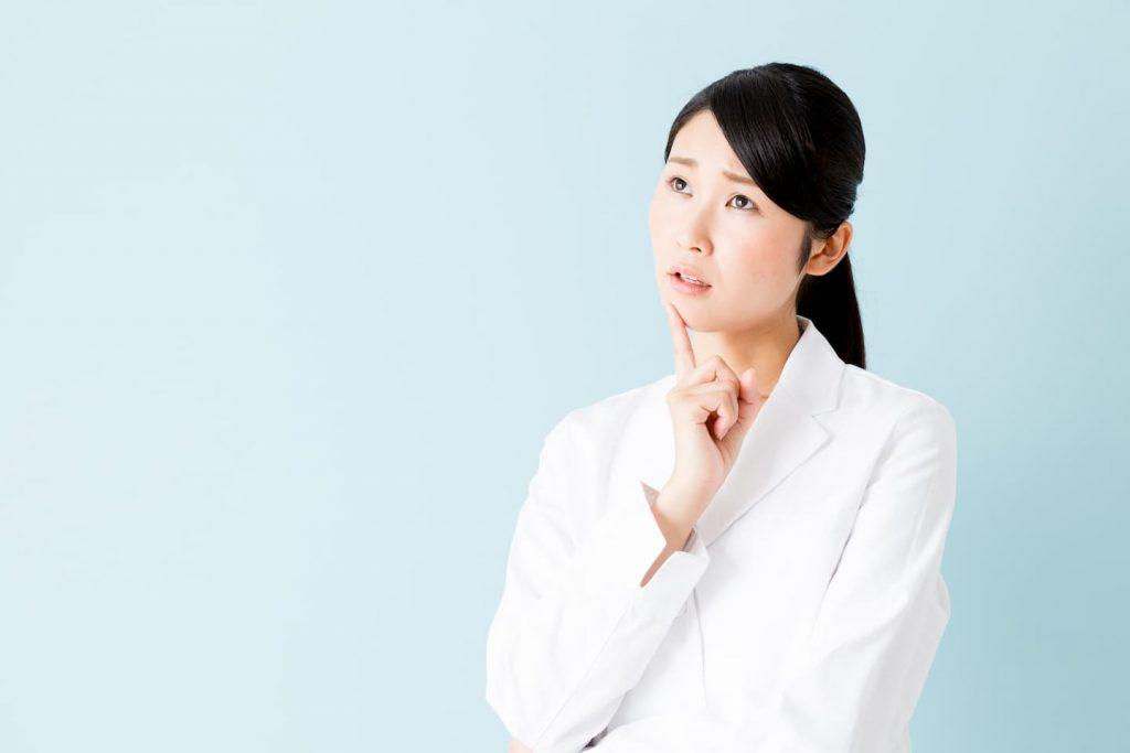 悩む白衣の女性