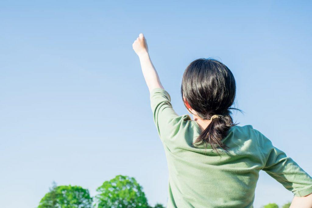 青空に向かって拳を上げる女性